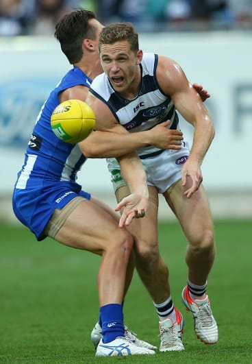Geelong captain Joel Selwood handballs the Roos' Ben Jacobs closes in.