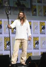 Jason Momoa poses with his Aquaman trident at Warner Bros' Justice League panel.