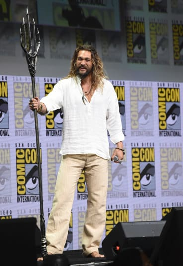 Jason Momoa poses with his Aquaman trident at Warner Bros' Justice League panel.