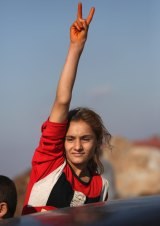 A Yazidi refugee celebrates news of the liberation of her homeland of Sinjar from IS extremists at a refugee camp in Syria.