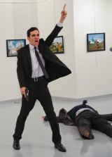 Turkish police officer Mevlut Mert Altintas gestures while shouting as the body of Russian Ambassador to Turkey, Andrei Karlov, lies at his side.