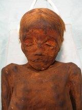A mummified blonde boy,  about five years of age.