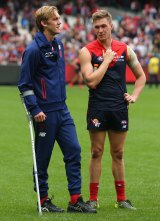Oscar McDonald talks to his brother Tom after injuring his ankle.