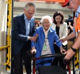 Mr Turnbull helps Frances Pearse, who will turn 100 tomorrow, onto a train carriage.