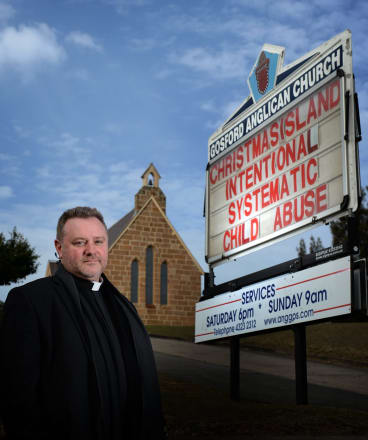 Father Rod Bower with one of his signs.