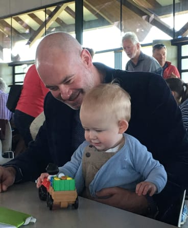 Anthony Toms, partner of Andrew Barr, entertains Andrew Barr's nephew, Angus, 10 months.