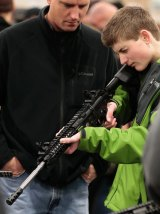 A boy holds a semi-automatic assault rifle while his father watches at a Utah gun show.