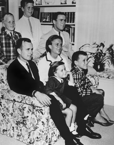 George H.W. Bush sits on the couch with his wife Barbara in 1964. George W. sits on the couch leg by his mother and Jeb is behind her.