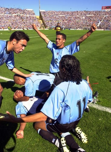 Uruguay's Dario Silva, on the ground, is embraced by teammates after scoring Uruguay's first goal.