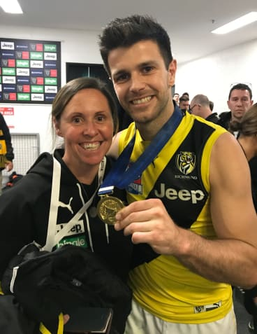 Emma Murray and Trent Cotchin pose with Cotchin's 2017 premiership medallion after the grand final.