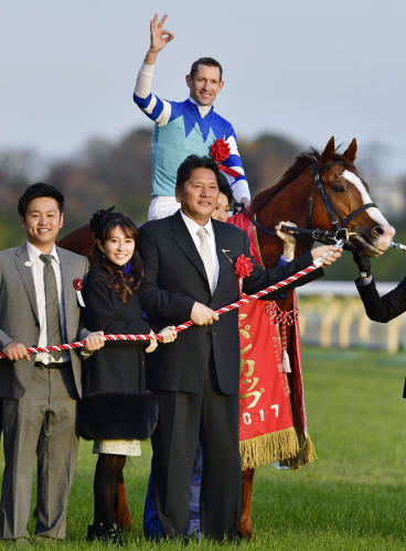 Top of the world: Hugh Bowman celebrates winning the Japan Cup on Cheval Grand.