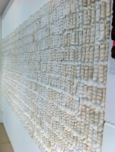 Small, white ceramic pieces of clay moulded from human knuckles on two walls of the gallery represent the 8709 Australian soldiers killed at Gallipoli.