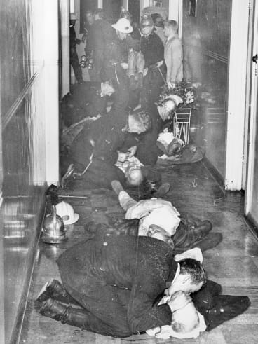 Firefighters, police and Salvation Army staff try to resuscitate victims on the night of the Salvos hostel fire.