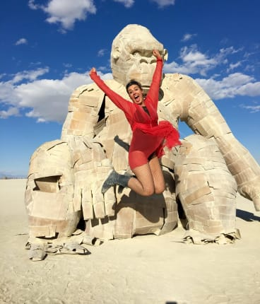 Carla O'Brien, pictured here with a sculpture at Burning Man.