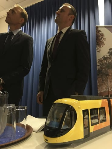 Simon Corbell, left, and Andrew Barr announcing the winning bidder for the Canberra tram, with a model of the Spanish-made trams.