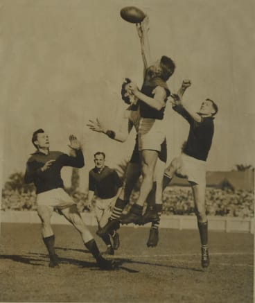 Mike Woods (centre) playing for Melbourne.