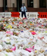 Police watched as the flowers were removed from the memorial.