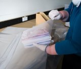 Sarah Lethbridge senior archivist demonstrates how to package the books for freezing.