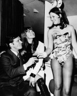 Hugh Hefner and girlfriend Barbi Benton, centre, are served by Playboy Club Bunny Cheri upon their arrival at La Guardia aboard the Big Bunny, Heffner's jet, in New York in March 1970 .