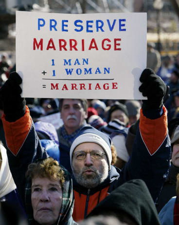 Southern Baptist minister Louis LoBue of  Massachusetts holds up a sign showing how he defines marriage.