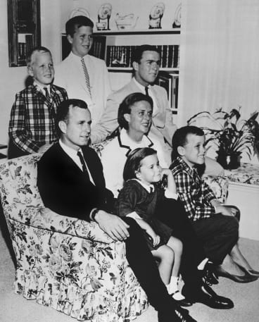 The Bush family in 1964. George H.W. Bush sits on couch with his wife Barbara and their children. George W. Bush sits at right behind his mother. Behind the couch are Neil and Jeb Bush.