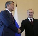 Putin smiles as he shakes hands with Atambayev.