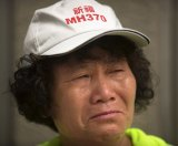 "A woman wearing a hat that says ""Pray for MH370"" cries outside the Ministry of Foreign Affairs in Beijing."