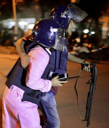 A member of Bangladeshi security personnel is taken for medical attention after gunmen attacked a restaurant  in a diplomatic zone of the country's capital Dhaka.