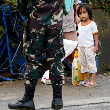 A girl looks at a soldier as people are stopped at a checkpoint in Marawi.