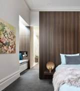 In this bedroom, the wardrobe has been concealed behind a dark-veneered timber blade wall. Photography by Peter Clarke; styling by Swee Lim.