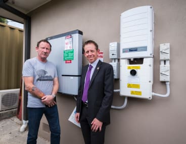 Alex Humphrys and Shane Rattenbury standing in front of the battery storage system.