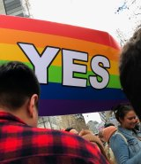 A rainbow-coloured 'Yes' flag flies at the Equal Love Rally in Melbourne's CBD.
