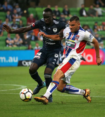 Victory's Thomas Deng puts pressure on the shot by Andrew Nabbout.