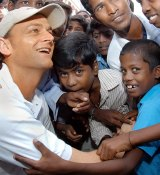 Former Australia captain Adam Gilchrist interacts with children during his visit to a slum in Madras October 12, 2004.