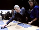 Apple CEO Tim Cook reaches for an Apple Watch to show to model Christy Turlington Burns during the Apple event in San Francisco.