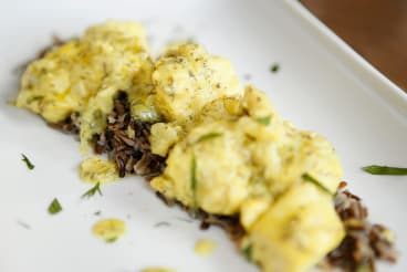 Cod served with wild black rice pilafi in lemon sauce.