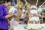 Sweet art: Judges in the esteemed Grand National Wedding Cake Competition check out an entry.