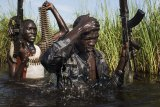 South Sudanese Nuer rebel soldiers patrol through a flooded area near the town of Bentiu. Unity State, South Sudan, 2014.