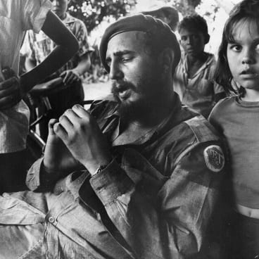 Fidel Castro as Cuban revolutionary leader relaxing at a sugar plantation near Havana, surrounded by children. Communist forces led by Castro overthrew Cuba's US-backed Batista government in 1959.