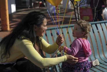 Elizabeth Kikkert gives a balloon to Ainsley Dawes, 23 months, of Evatt.