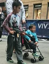 A boy walks through Martin Place with a toy AK-47.