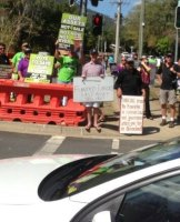 Former Young LNP leader Ben Riley stands with a satirical sign alongside demonstrators.