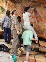 Melbourne University scientists Helen Green, Jordy Grinpukel, traditional owners Mark Unghango, Ernie Boona and Damien Fink sampling a hard-to-reach mineral crust.