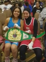 Aliyah Charbonier (L) presenting Amaiya Zafar (R) with the belt she was awarded after Zafar was disqualified from their fight for wearing a hijab.