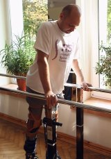 Darek Fidyka walks with the assistance of parallel bars and leg braces.