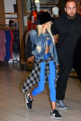 Pia Mia hides her face as she walks through Sydney Airport on Saturday.
