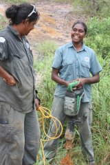 Indigenous rangers promote and maintain tourist sites, like Yupunu Marika and Grace Wunungmurra, installing tables and fences at Giddies River recreational area in NE Arnhem Land.
