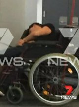 The man appears to be slumped over on airport seats next to a wheelchair.