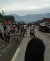 Protesters hurl rocks at the confrontation in Linshui.