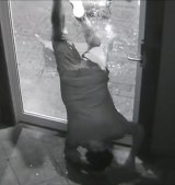 The man went almost vertical as he squeezed himself through the hole he had made in the glass door.